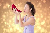 Elegant brunette kissing a shoe against yellow abstract light spot design