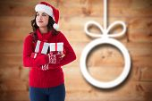Thoughtful brunette holding many gifts against blurred christmas decorations on wood