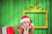 Thoughtful woman lying between shopping bags against blurred christmas background