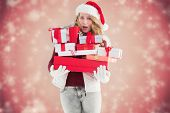 Blonde woman in trouble holding pile of gifts against white snowflake design on red