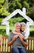 Mature couple hugging in the garden against house outline in clouds