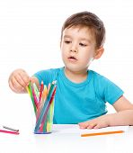 Cute Boy Is Drawing Using Color Pencils