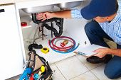 picture of plumber  - Plumber with Plumbing tools on the kitchen - JPG