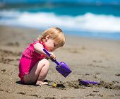 little cute girl playing in the sand with a shovel on the beach on a beautiful summer day