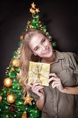 Portrait of cute blond female near beautiful decorated Christmas tree over dark background, holding in hands little golden gift box, happy holidays concept