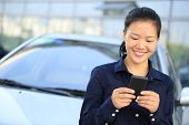 asian businesswoman use smart phone leaning on car/outside of office building