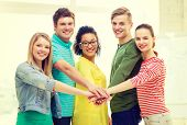 education and friendship concept - five smiling students with hands on top of each other