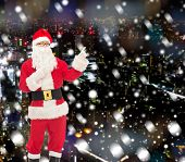 christmas, holidays, gesture and people concept - man in costume of santa claus pointing fingers over snowy night city background