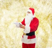 christmas, holidays and people concept - man in costume of santa claus with notepad and pen over yellow lights background