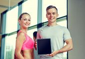 fitness, sport, advertising, technology and diet concept - smiling young woman and personal trainer with tablet pc blank screen in gym