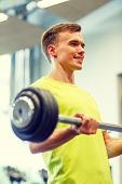 sport, fitness, lifestyle and people concept - smiling man doing exercise with barbell in gym