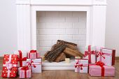 Present boxes near the fireplace with firewood on wooden floor and whit wall background