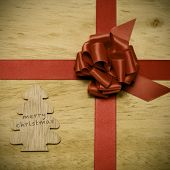 the text merry christmas written in a tree-shaped piece of wood and a red ribbon bow on a wooden surface