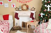 Beautiful Christmas interior with sofa, decorative fireplace and fir tree