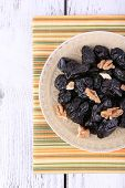 Plate of prunes and walnut on striped napkin with shell on color wooden background