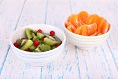Bowl of slices kiwi and mandarin with currants on color wooden background