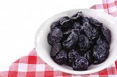 Purple bowl of prunes on checkered napkin isolated on white