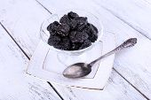Glass bowl of prunes on white plate with spoon on color wooden background