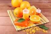 Spa still life with oranges, bottles of bath salt and oil, and bar of soap on striped napkin on wooden background