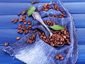Green petals near the spoon of coffee beans on blue wooden background with jeans material