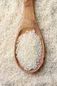 High angle closeup shot of a wooden spoon full of uncooked rice grains laying on a bed of grain. Vertical format.