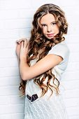 Pretty teenager girl with beautiful long curly hair wears white knitted dress. Beauty, fashion.