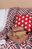 Hand-made Christmas gifts and decorations on plaid in room
