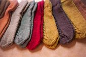 Colorful Woolen Knitted Mittens Lying On The Counter