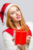 Beautiful young woman holding in front a Christmas present.