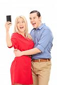 Vertical shot of an excited couple taking a selfie with mobile phone isolated on white background