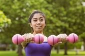 Portrait of healthy and beautiful young woman lifting dumbbells in park