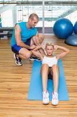 Male trainer assisting young woman with abdominal crunches at fitness studio