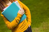 Mid section of female college student with books in the park