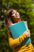 Portrait of smiling female college student with books in the park