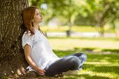 Pretty redhead sitting and thinking in park
