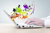 Hands of businessman using laptop and colorful splashes on screen