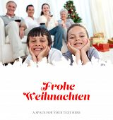Brother and sister on floor with their family in Christmas against christmas greeting in german