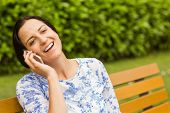 Smiling brunette sitting on bench phoning in the park