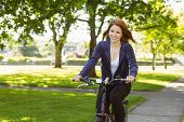 Pretty redhead cycling a bike on a sunny day