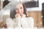 Brunette in white wool jumper posing against fir tree forest and snowflakes