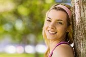 Fit blonde leaning against tree smiling on a sunny day