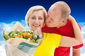 Mature man kissing his partner holding flowers against bright blue sky over clouds