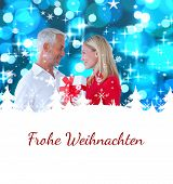 loving couple with gift against christmas greeting in german