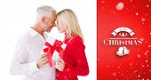 Smiling couple passing a wrapped gift against red vignette