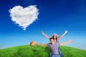 Man giving his pretty girlfriend a piggy back against cloud heart