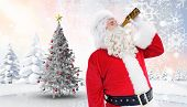 Father christmas drinking a beer against christmas tree in snowy landscape