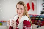 Portrait of woman having coffee on couch against snow