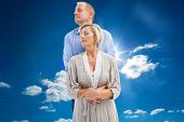 Happy mature couple embracing with eyes closed against cloudy sky with sunshine