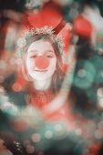 Festive little girl wearing red nose against digitally generated twinkling light design