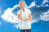 Happy mature woman smiling at camera against cloudy sky